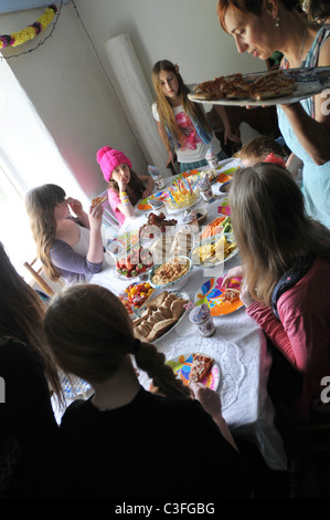 A mother serving food at an 11 year old girls birthday party - Stock Photo
