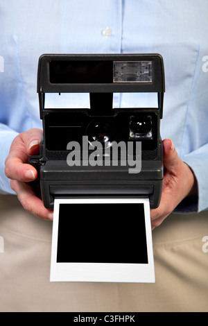 Photo of a woman holding an instant camera with a blank print to add your own image,clipping path included for the - Stock Photo