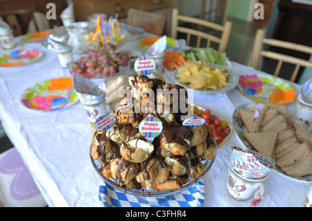 Home made profiteroles made for a child's birthday  placed on a table set for a party - Stock Photo