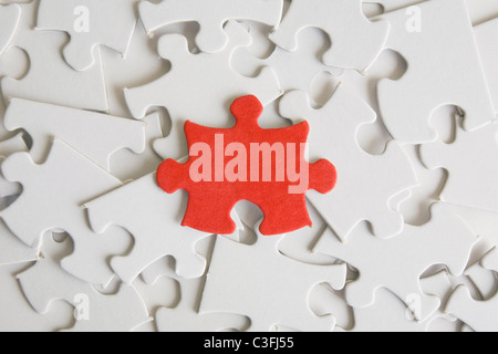One red jigsaw piece on a pìle of blank ones.  - Stock Photo