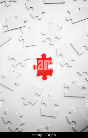 One red jigsaw piece oamong blank ones. - Stock Photo