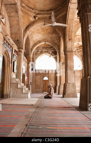 Man praying in a mosque, Siddi Sayed Mosque, Ahmedabad, Gujarat, India - Stock Photo