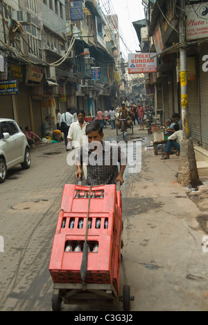 Man pushing crates of soft drink bottles on a cart, Chandni Chowk, Delhi, India - Stock Photo