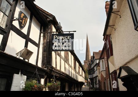 Church Lane Ledbury, Prince of Wales pub sign and church spire in the background. Herefordshire, England, UK - Stock Photo