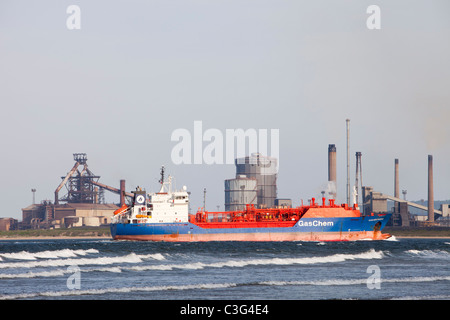 A Gaschem ship full of LPG sails into Teesmouth harbour past the Redcar Steel works, Teeside, UK. - Stock Photo