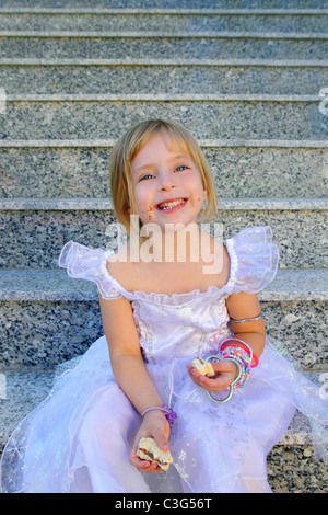 blond children girl eating chocolate sandwich princess dress on granite stairs - Stock Photo