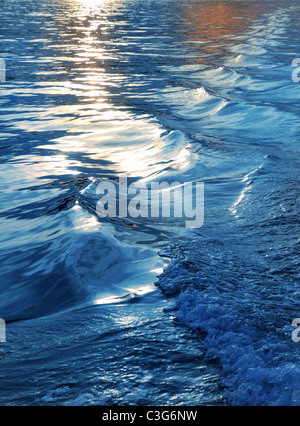 blue sea water waves sunset from boat stern ship wake - Stock Photo