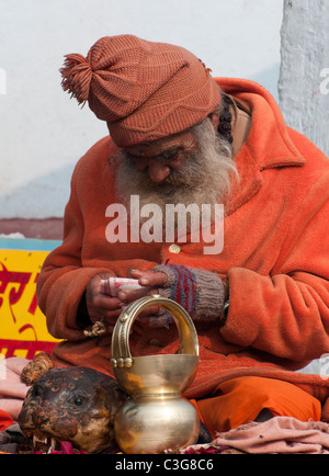 Sadhu counting his takings at the Bindhya Basini Mandir Temple in Pokhara, Nepal - Stock Photo