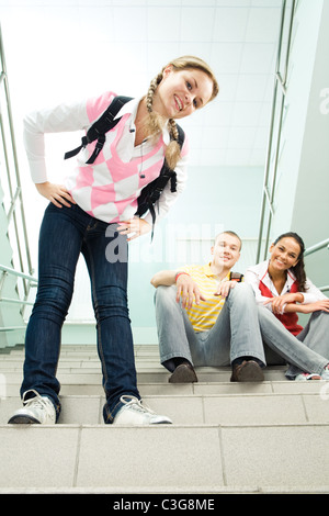 View from below of pretty student standing on stairs and looking at camera with her friends sitting behind - Stock Photo