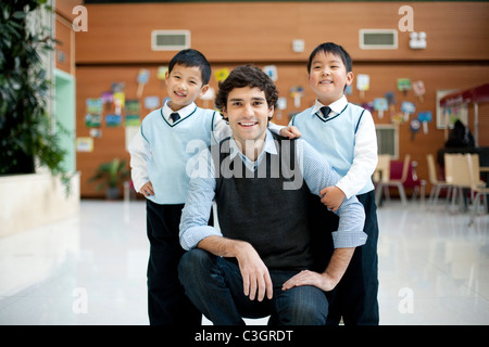Teacher and two young students posing in campus - Stock Photo