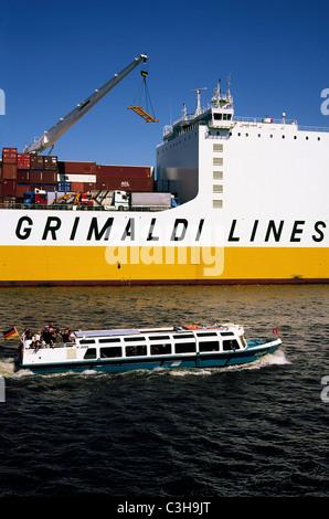 A sightseeing barge passes Grimaldi's Grande Congo at Hansahafen in the German port of Hamburg. - Stock Photo
