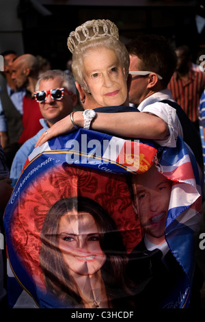 People wearing the mask of Queen Elisabeth and a flag of Prince William and Kate to celebrate their wedding, Soho, - Stock Photo