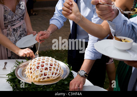 Guests enjoying cake at wedding reception - Stock Photo
