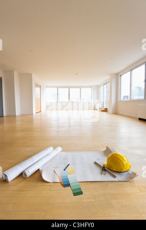 Blueprint, color swatch and hardhat on floor in empty room - Stock Photo