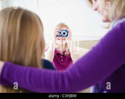 Mother and daughters (8-11) taking pictures - Stock Photo