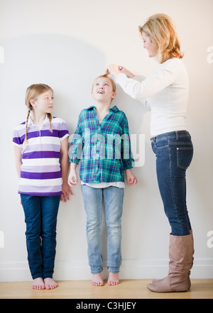 Mother measuring daughters' (8-11) height - Stock Photo