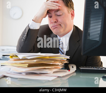 Businessman looking at stack of folders - Stock Photo