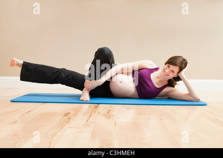 Young pregnant woman exercising - Stock Photo