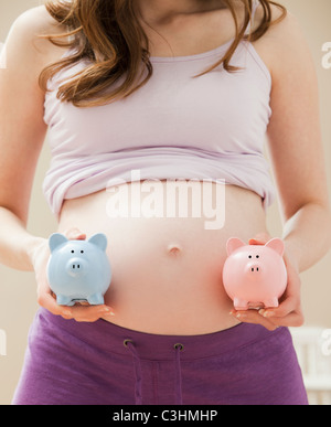 Young pregnant woman holding blue and pink piggybanks - Stock Photo