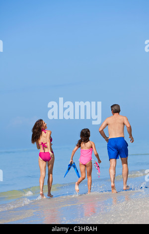 Rear view of a happy family of mother, father and child, a daughter, running holding hands and having fun in waves - Stock Photo
