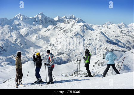 Skiers on the top of the Kratki plaz piste at the Vogel Ski Centre in the Triglav National Park of Slovenia - Stock Photo