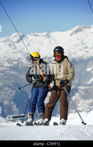 Two boys on a drag lift at the Vogel Ski Centre in the Triglav National Park of Slovenia - Stock Photo