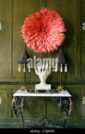 Medusa bust on marble top console table against green panelled wall with red feather hat above - Stock Photo