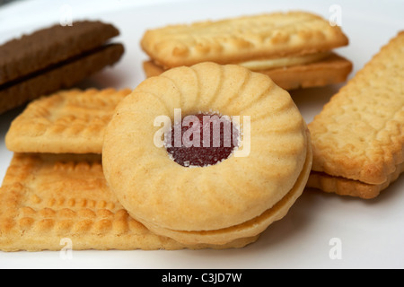 assorted british biscuits on a plate including a jammie dodger - Stock Photo