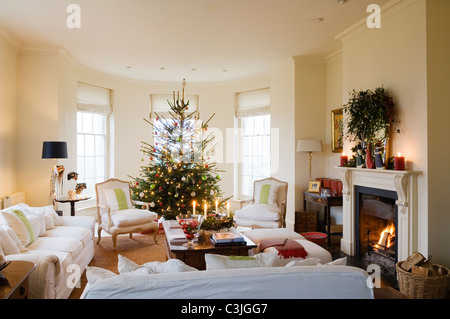 Christmas tree decorated with baubles in regency living room with armchairs and fireplace - Stock Photo