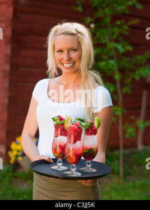 Woman holding tray of cocktail glasses - Stock Photo