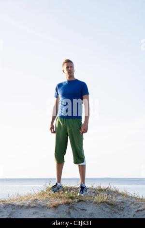 A man standing on a beach, Malmo, Skane, Sweden. - Stock Photo