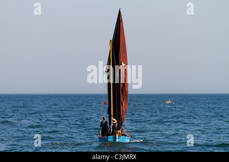 A Beer Lugger setting off from Beer beach in Devon - Stock Photo