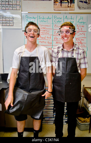Two happy high school chemistry students in San Clemente, CA, are equipped for a laboratory experiment wearing safety - Stock Photo