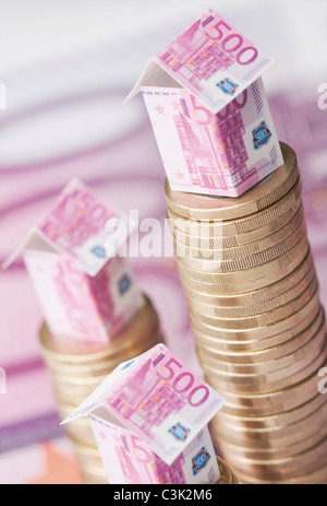 Building of 500 euro notes on stack of coins - Stock Photo