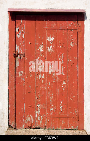 red door weathered old paint peel latch hinge slats planks wooden keyhole white wall entrance locked heavy secure - Stock Photo