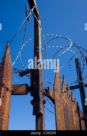 security fence rust spike top barb wire blue sky row keep out deterrent safe block sharp injury do not enter - Stock Photo