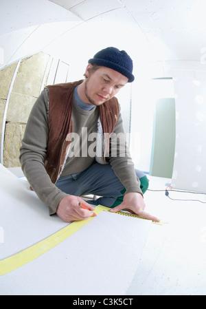 Man measuring a plasterboard panel - Stock Photo