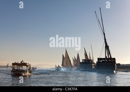 Dahabiyahs, launches, taxis and felucca moored on the West Bank of the Nile River at Sunset in Luxor Egypt - Stock Photo