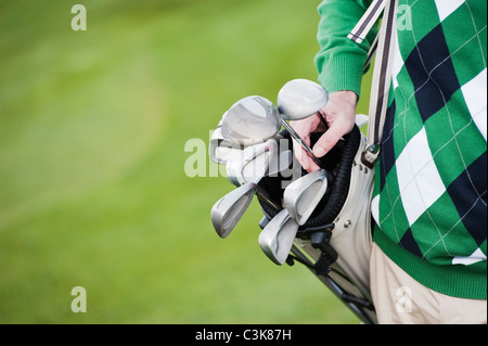 Italy, Kastelruth, Mature man with carrying golf bag, close up - Stock Photo