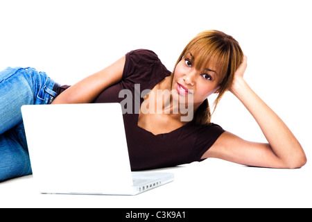 Woman lying on the floor and working on a laptop isolated over white - Stock Photo