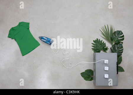 Iron connection to electric sockets with leaves, t-shirt on gray background - Stock Photo
