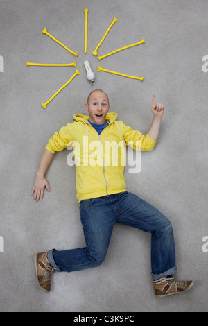 Young man pointing at electric bulb, portrait - Stock Photo