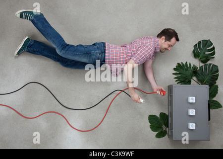 Mid adult man holding plug near electric socket - Stock Photo