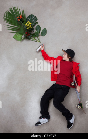 Boy spraying leaves from spray bottle - Stock Photo