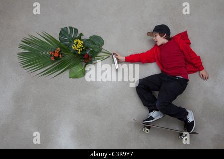 Boy spraying leaves from spray bottle - Stock Photo