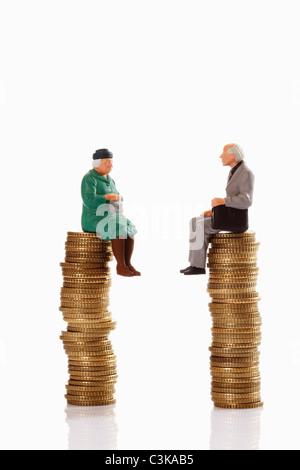 Figurines grandma and grandpa sitting on coin stack - Stock Photo