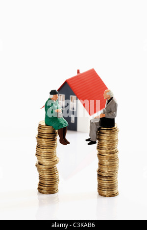 Figurines grandma and grandpa sitting on coin stacks in front of model house - Stock Photo