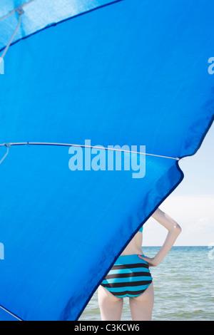 Woman behind blue beach umbrella - Stock Photo