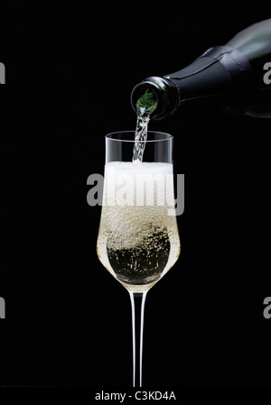 Champagne being pouring into glass from bottle, close-up - Stock Photo