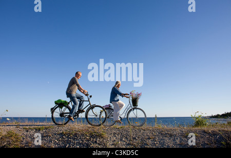 Mature couple riding bicycle on beach - Stock Photo